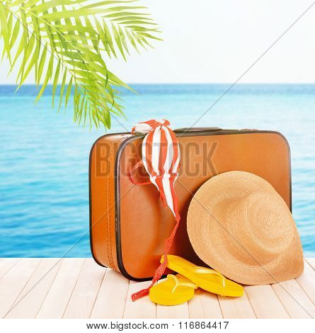 Vintage valise with summer items on wooden board on sea background