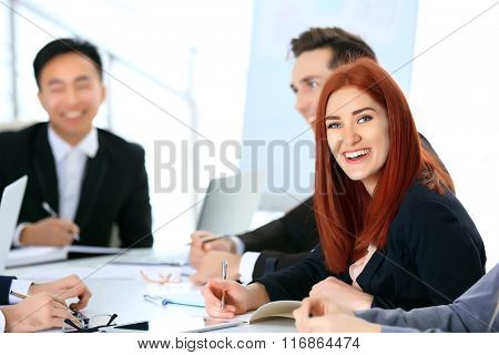 Young redhead businesswoman sitting at the office meeting