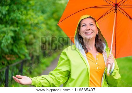 Portrait Of A Beautiful Girl With An Umbrella And A Raincoat On The Nature