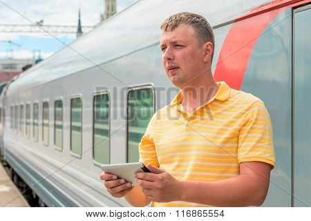 Middle-aged Man With A Tablet Beside The Train