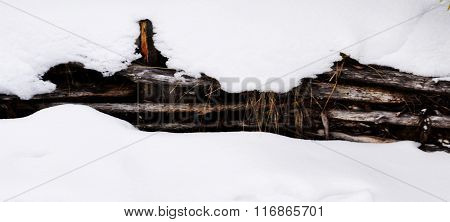 Wooden fence covered with snow