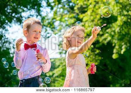Sister And Brother In The Park With Soap Bubbles