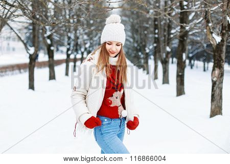 Pretty Woman In A Red Sweater, A White Cap And A Jacket, Knitted Scarf Walks Near A Tree In The Park