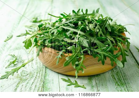 Fresh Green Arugula In Bowl On Wooden Table