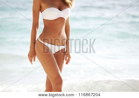 Woman with perfect body in bikini on sea background