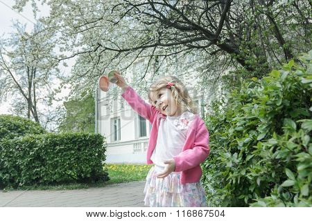 Outdoor portrait of joyful blonde girl at blooming fruit tree and porch background