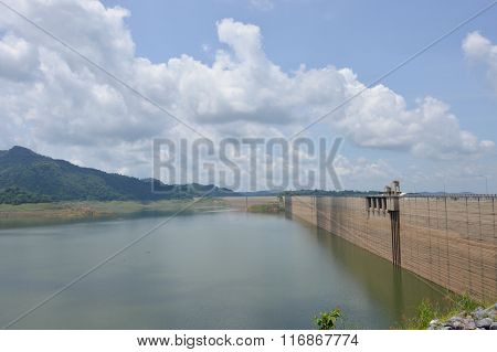 concrete dam in forest on sunshine day