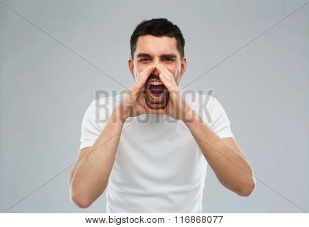 angry shouting man in t-shirt over gray background