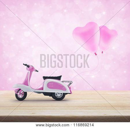 Pink Scooter Toy With Pinkl Heart Love Balloon On Wooden Table Over Light Pink Heart Bokeh Backgroun