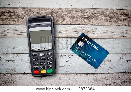 Payment Terminal And Credit Card On Wooden Background