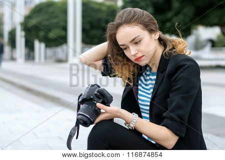 Girl Sitting On The Sidewalk And Watched The Pictures On Her Camera