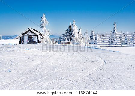 Vacation rural winter background with small wooden alpine house, white pines, fence, snow field, mou