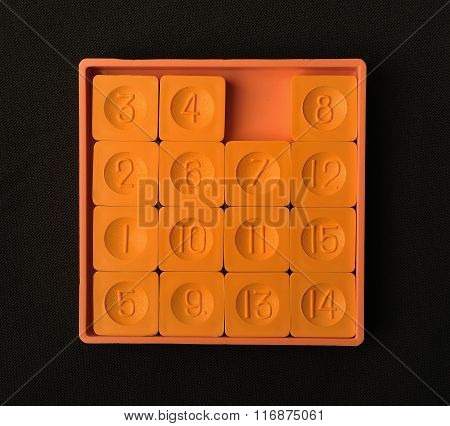 Pocket sliding fifteen puzzle game orange color on a dark background