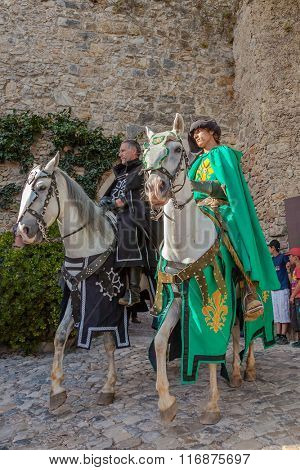 Obidos, Portugal - August 09, 2015: Knights riding white horses in the parade of the Medieval Market reenactment. The Medieval Market festival is very popular among tourists.