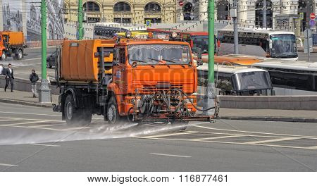 Watering machine orange color washes the streets of Moscow, utilities