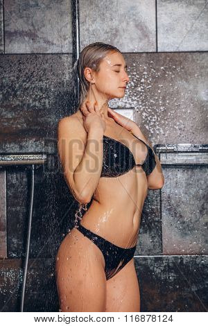 Beautiful woman standing at the shower. In a black bathing suit