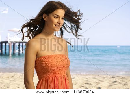 Happy young casual caucasian woman standing at the sandy summer beach. Smiling, copyspace.