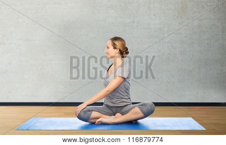 woman making yoga in twist pose on mat