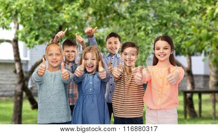happy children showing thumbs up over backyard