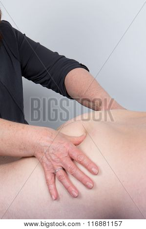Physio Manipulating The Buttock Of A Patient In A Room