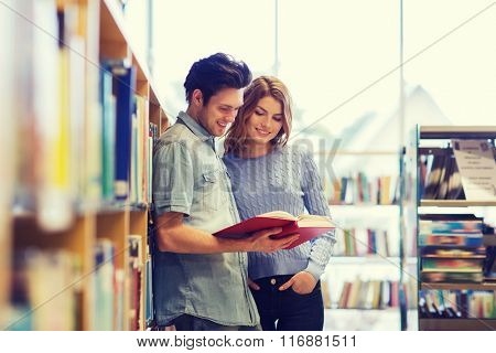 happy student couple with books in library