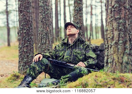soldier or hunter with gun sleeping in forest