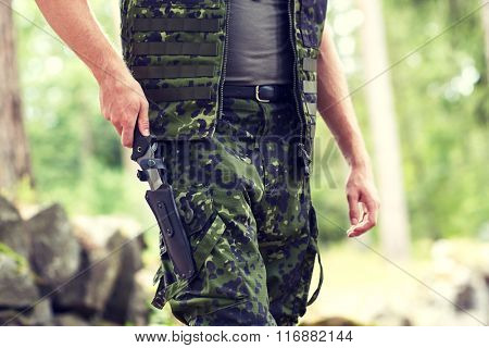 close up of soldier or hunter with knife in forest
