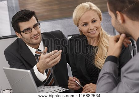 Smart businesspeople having meeting, talking, smiling.