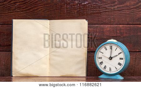 Retro alarm clock and book with wood board background