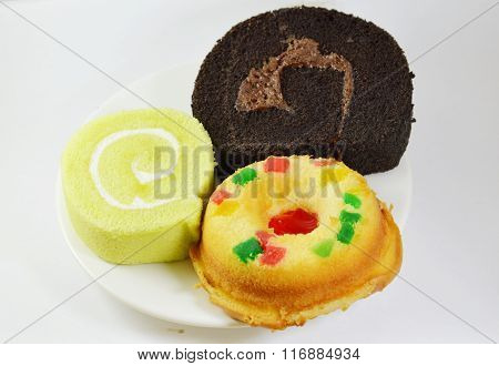 pandan cake and strawberry roll with chocolate cake roll on dish