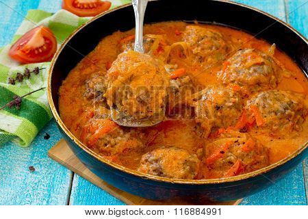 Homemade Meatballs In Tomato Sauce And Basil On A Wooden Table