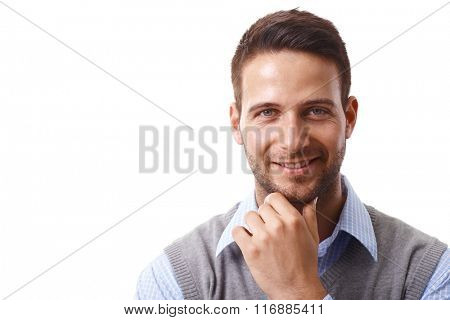 Closeup portrait of handsome young businessman smiling happy, looking at camera, hand on chin.