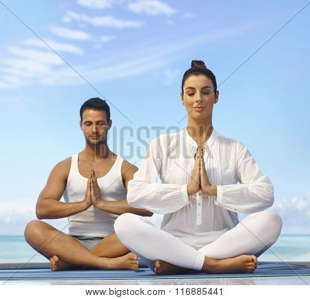 Young couple meditating on the beach eyes closed.