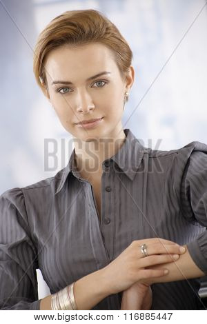 Closeup portrait of attractive young businesswoman, looking at camera.