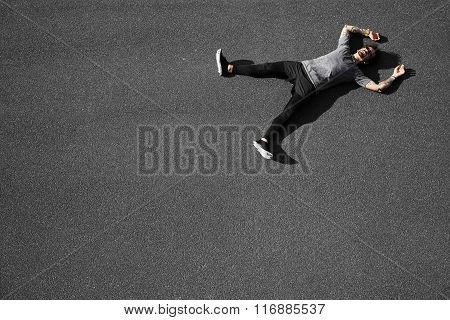 Sport Fitness Man Relaxing After Training. Athlete Resting Sitting In Asphalt After Running And Exer