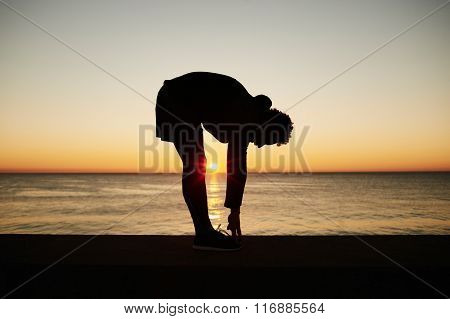 Young Muscular Build Man Doing Stretching Exercise On The Beautiful Sea Background During Sunset, At