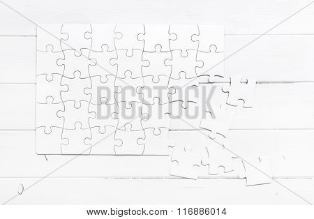white unfinished puzzle isolated on white wooden table