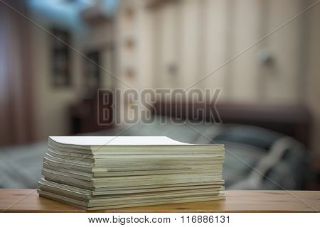 stack of old magazines on wooden table in the bedroom