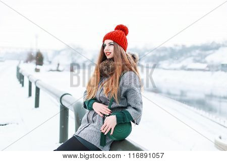 Beautiful Stylish Woman In The Fashion Warm Clothing Sitting On A Background Of A Snowy Landscape