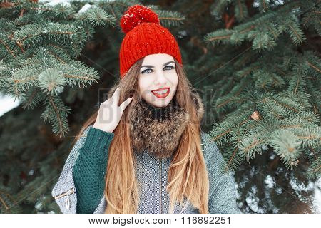Young Beautiful Girl With Red Lips And A Knitted Hat In Winter Coat Standing Near Tree
