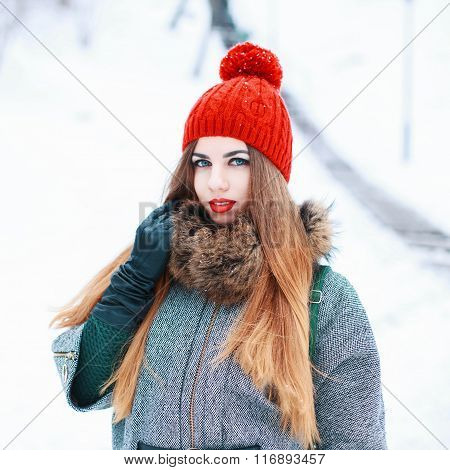 Young Beautiful Girl With A Red Hat And Coat In Winter Snowy Day
