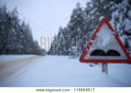 blurred image snowy winter forest route. traffic sign rough road