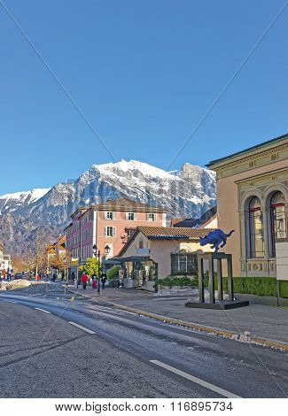 BAD RAGAZ SWITZERLAND - JANUARY 5 2015: Cat statue and Mountain. Bad Ragaz is a city in St. Gallen in Switzerland. It lies over Graubunden Alps. Spa and recreation is at the end of Tamina valley