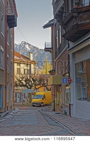 Street view and Alps in the City of Bad Ragaz. Bad Ragaz is a city in canton St. Gallen in Switzerland. It lies over Graubunden Alps. Spa and recreation village is at end of Tamina valley