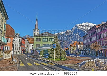 Catholic Church and Mountains in Town of Bad Ragaz. Bad Ragaz is a city in canton St. Gallen in Switzerland. It lies over Graubunden Alps. Spa and recreation village is at end of Tamina valley