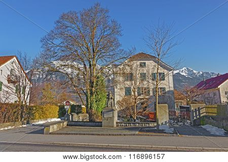 Monument of a Man and Alps Mountains in Bad Ragaz. Bad Ragaz is a city in canton St. Gallen in Switzerland. It lies over Graubunden Alps. Spa and recreation village is at end of Tamina valley
