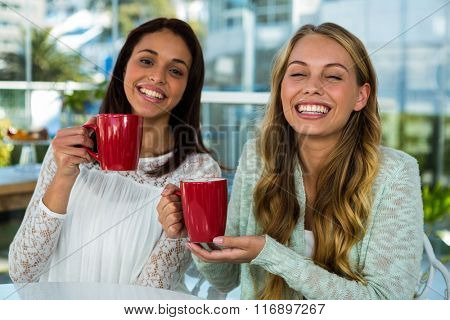 two girls drink tea at home