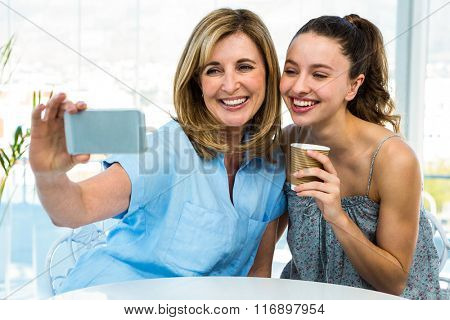 mother and daughter take selfie with a phone