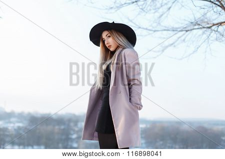 Young Stylish Girl In A Hat And Coat Stands On A Hill On A Background Of A Winter Landscape
