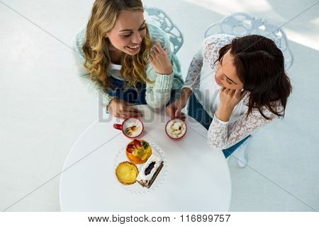 two girls drink coffee and eating pastries